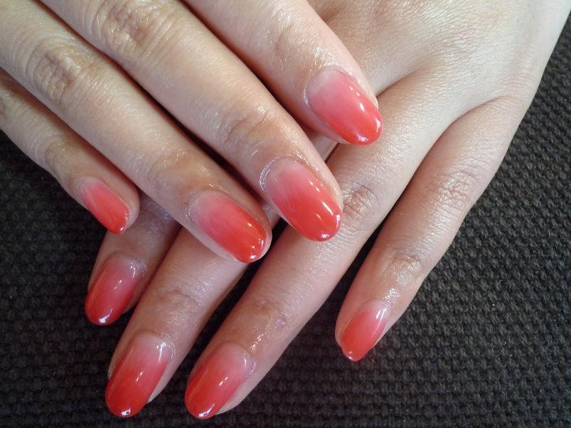 鮮やかなピンクオレンジのグラデーションネイルです。